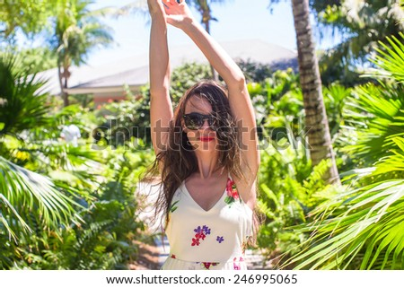 Young woman on summer vacation at lush garden - stock photo