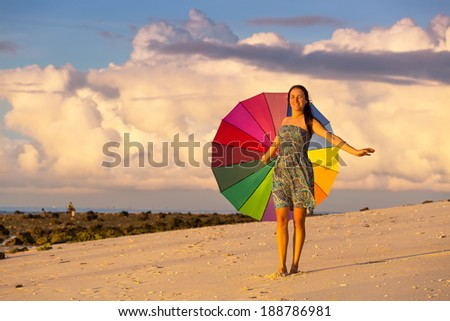 young woman on the beach in summer with a colorful umbrella on a background of blue sky with clouds