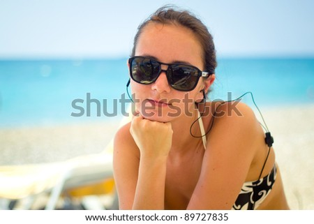 Young woman on the beach listening to music - stock photo
