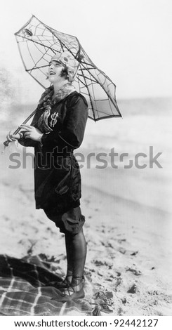 Young woman on the beach with an umbrella  looking like a spider web