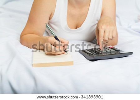 young woman on the bed with a notebook and calculator.Credit, mortgage. Family budget. - stock photo