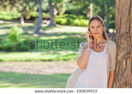 Young woman on the cellphone leaning against a tree