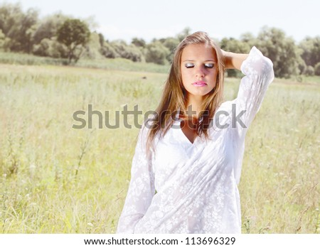 Young woman on the field with flowers - stock photo