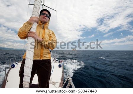 Young woman on the front of a yacht during sail on the sea - stock photo