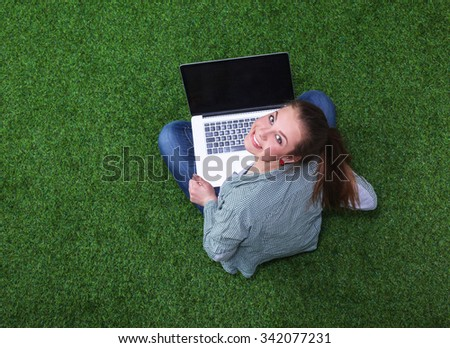 Young woman on the grass in park or garden with laptop