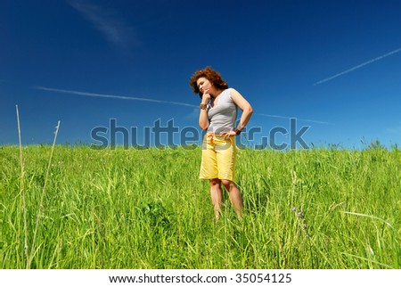 Young woman on the green field thinking - stock photo