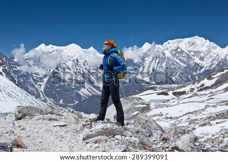 Young woman on the hiking path in the mountains of Nepal - Himalayas. Background Annapurna range