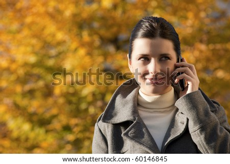 Young woman on the phone, Autumn background