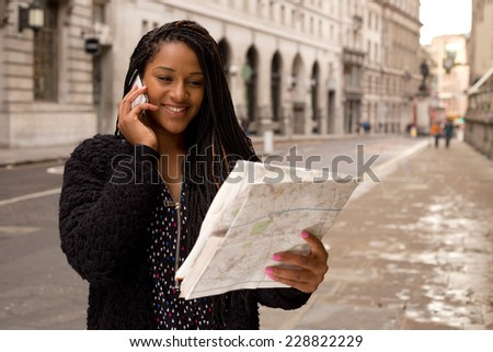 young woman on the phone holding a map - stock photo