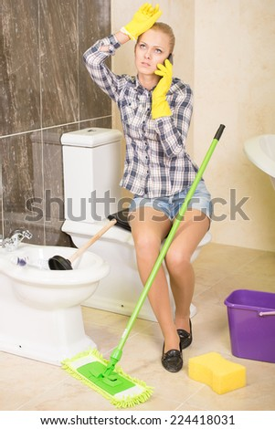 Young woman on the phone in the toilet cleaning. - stock photo
