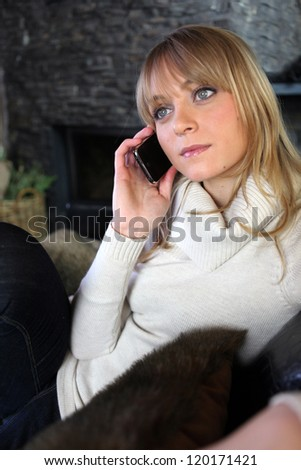 Young woman on the phone on a couch - stock photo