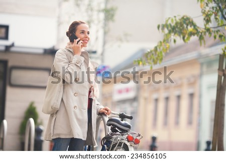 Young woman on the phone standing next to the bicycle on the street - stock photo