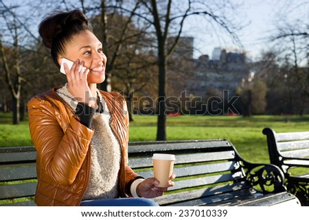 young woman on the phone with a coffee in the park - stock photo