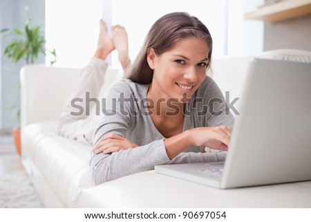 Young woman on the sofa reading e-mail - stock photo