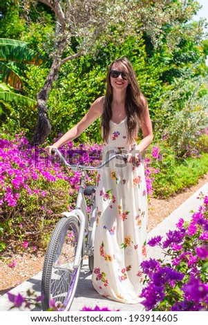 Young woman on vacation biking at flowering garden - stock photo