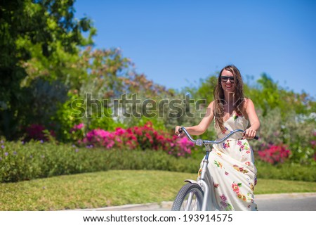 Young woman on vacation biking at lush garden - stock photo