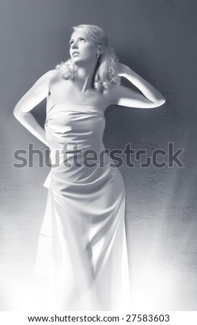Young woman on wall background. Black and white. - stock photo
