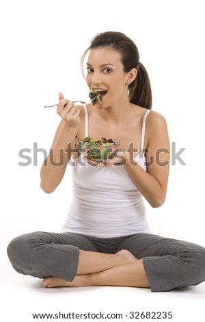 Young woman on white background with a salad - stock photo