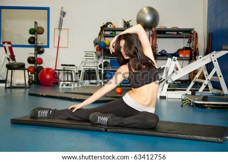 young woman on yoga mat in gym - stock photo