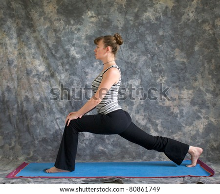 Young woman on yoga mat in woman doing Yoga posture high Lunge with hands on knee, against a grey background in profile, facing left lit by diffused sunlight. - stock photo