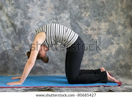 Young woman on yoga mat in  Yoga posture Marjaryasana or cat pose against a grey background in profile, facing left lit by diffused sunlight. - stock photo