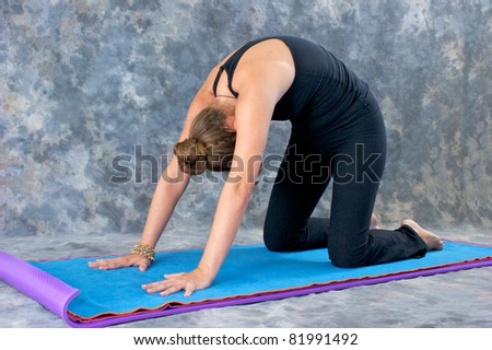 Young woman on yoga mat in  Yoga posture Marjaryasana or cat pose against a grey mottled background .