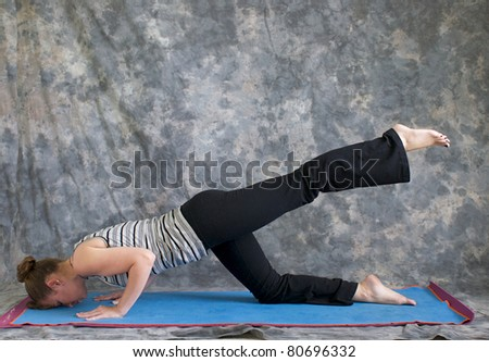 Young woman on yoga mat in  Yoga posture sunbird pose with left leg lifted, against a grey background in profile, facing left lit by diffused sunlight. - stock photo