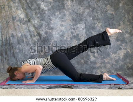 Young woman on yoga mat in  Yoga posture sunbird pose with right leg lifted, against a grey background in profile, facing left lit by diffused sunlight. - stock photo