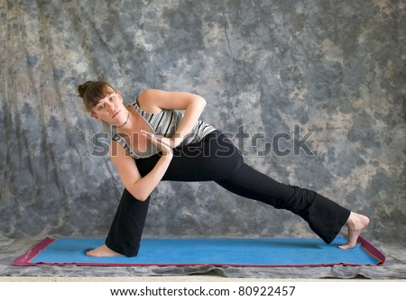 Young woman on yoga mat Yoga posture Parivrtta Parsvakonasana or Revolved Extended Side Angle pose with hands in prayer position against a grey background, facing left lit by diffused sunlight. - stock photo