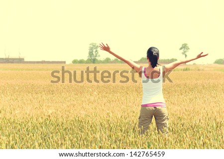 young woman open arms at wheat field