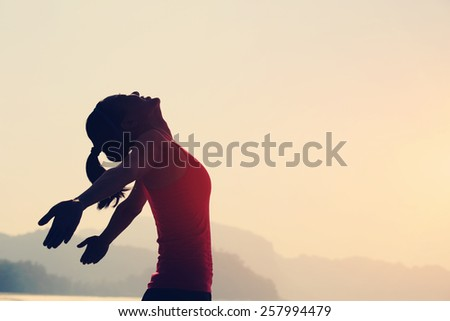 young woman open arms under the sunrise at seaside - stock photo