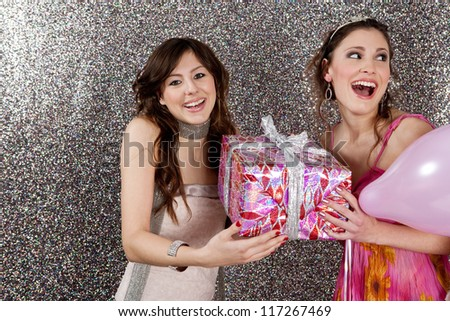 Young woman opening a gift at her birthday party, against a silver glitter background. - stock photo