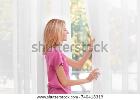 Young woman opening silk curtains in room