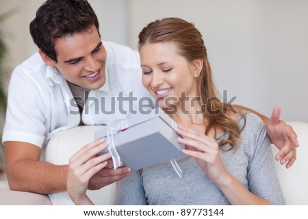 Young woman opening the gift she got from her boyfriend - stock photo