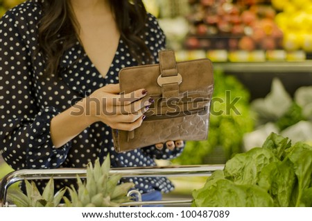 Young woman opening wallet at the supermarket - stock photo
