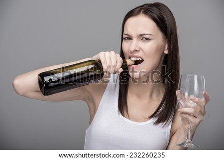 Young woman opens a bottle of wine by teeth. Concept of bad habits. - stock photo