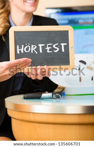 Young woman or acoustician holding a board or a board advertising a hearing test (in german language), besides her is a selection of hearing aids - stock photo