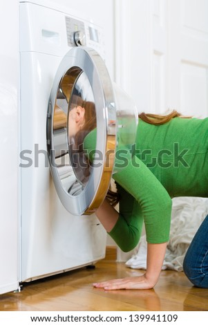 Young woman or housekeeper has a laundry day at home, she is searching for the lost socks - stock photo