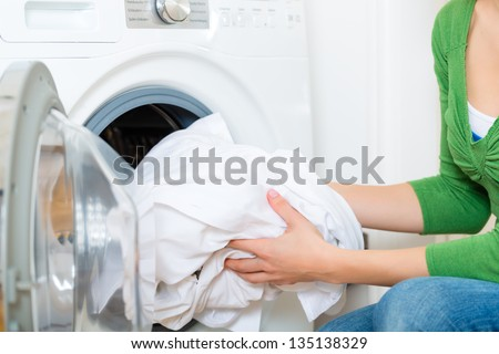 Young woman or housekeeper has a laundry day at home, she takes the laundry or whites out of your washing machine or the dryer - stock photo