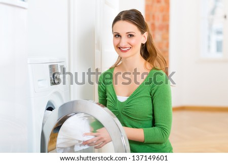 Young woman or housekeeper has laundry day at home, she takes the out of the washing machine or the dryer - stock photo