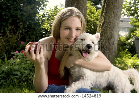 Young woman or teenager hugging her dog outdoors and playing with an apple