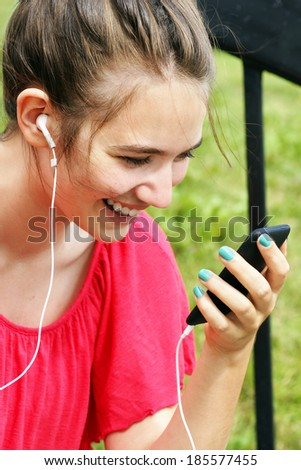 Young woman or teenager listening to music of talking to a friend using mobile cell phone - stock photo
