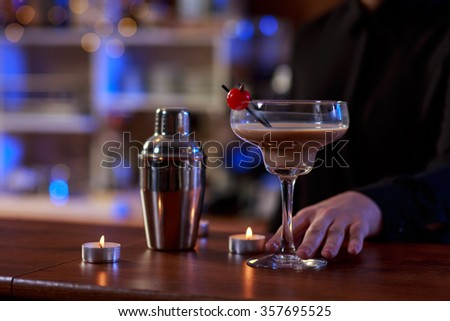 Young woman ordering a drink in bar - stock photo