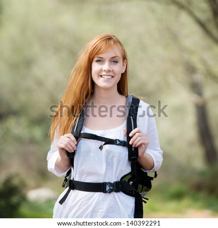 Young woman out hiking with a rucksack enjoying the exercise in a healthy lifestyle concept - stock photo