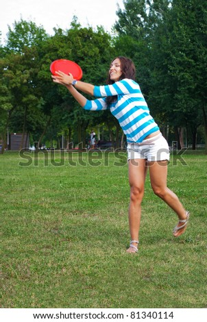 Young woman outdoor catching a frisbee - stock photo