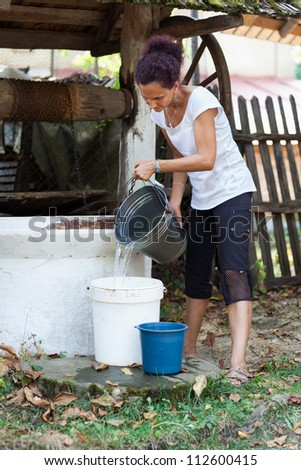 Young woman outdoor getting water from a vintage wooden well with pulley - stock photo