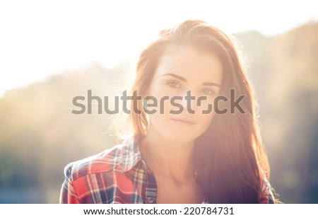 Young woman outdoor portrait in soft sunny daylight
