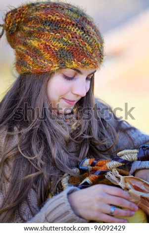 Young woman outdoor with a basket of fruits in autumn. - stock photo
