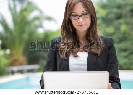 Young woman outdoor with laptop and reading glasses at a swimming pool