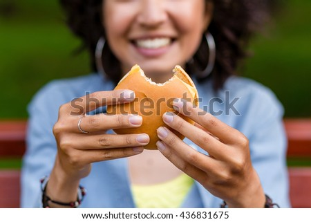 young woman outdoors eating a fast food hamburger. Focus on the burger, woman is blurred - stock photo